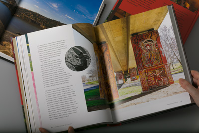 Designer holding the book open to show pages 78–79 featuring artist Kym Freeman.