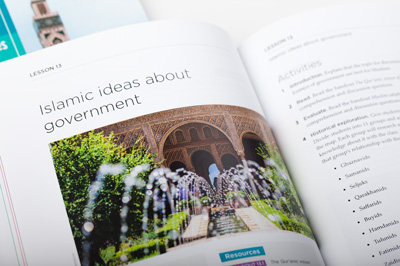 Photograph of an open student book showing the internal design and another book blurred in the background showing the cover design.
