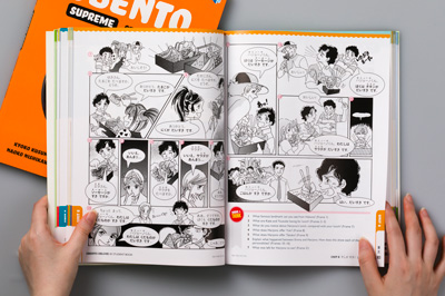 Photo of a double page spread showing manga illustration in the Obento Deluxe Student Book.
