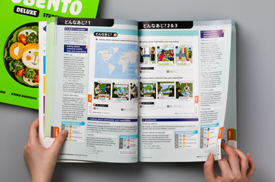 Photo of the teacher toolkit book held open, showing the wraparound version of the student book with margin notes.
