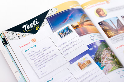 Photograph of a student book page showing a design representing a real-life postcard.