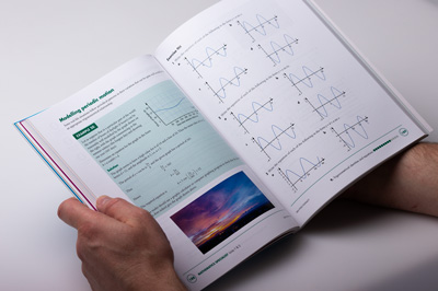 Maths book held open. You can see the theory section and example on the left page, and the exercise on the right page. There are many design elements on the the page spread, including a coloured text box, paragraphs of text, a photographic image and mathematical graphs.