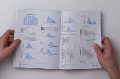 A designer holding the maths book open at the answer section, showing the two-column layout of a double-page spread.
